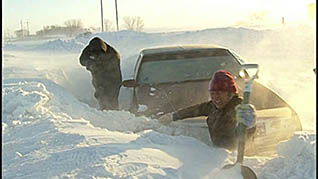 Two men with shovels attempt to dig a sedan out of a deep snow bank