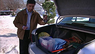 A man hovers over the open trunk of a car showing items necessary to be safe winter driving