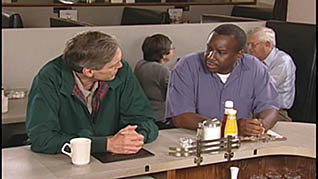 Two men sitting at a diner counter talking about defensive driving