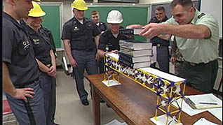 A man in a military uniform shows a group of construction workers one of the leadreship lessons he learned at West Point