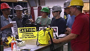 Workers in hard hats receiving H2S training