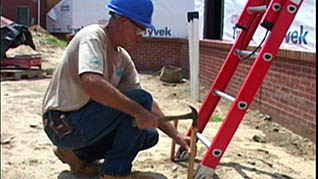 Working on a ladder safely while on uneven terrain
