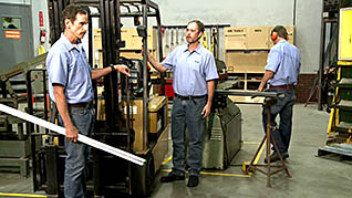 Two men standing in front of a fork lift