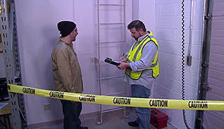 A man in a bright yellow safety vest interviews a man in a windbreaker and a knit cap for an accident investigation case study