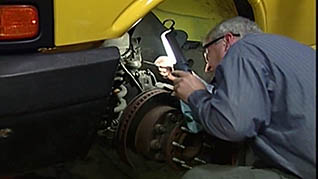 A worker inspects a car in the mechanic safety training video