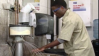 An auto worker washes his hands in the mechanic safety training video